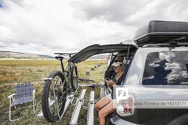 Erwachsene Frau sitzt mit Mobiltelefon in einem SUV