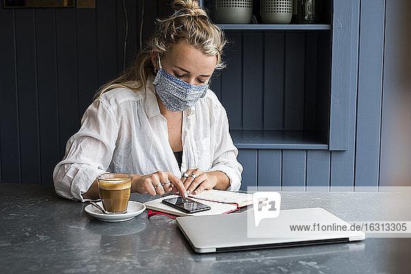 Frau mit Gesichtsmaske  die allein an einem Café-Tisch sitzt und einen Laptop benutzt  der aus der Ferne arbeitet.
