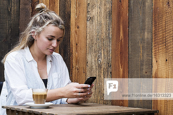 Junge blonde Frau  die allein in einem Café sitzt  ein Mobiltelefon benutzt und aus der Ferne arbeitet.