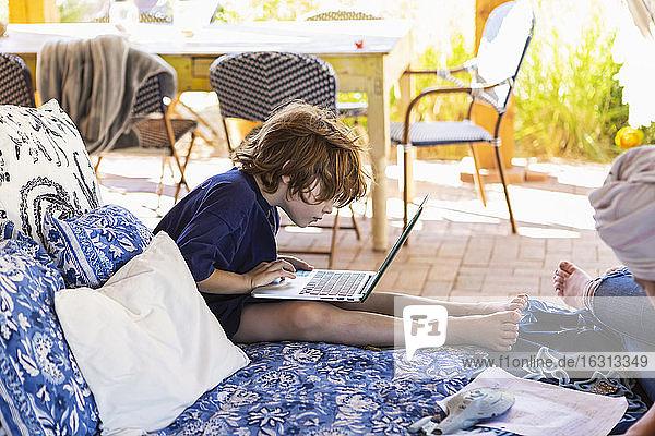 Junge mit braunen Haaren sitzt auf einem Bett im Freien und macht Hausaufgaben am Laptop.