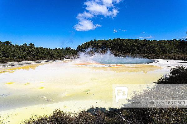 Große Thermalbecken mit aufsteigenden Nebeln und gelben Schwefelablagerungen