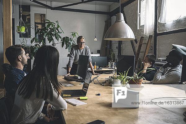 Geschäftsfrau diskutiert mit Kollegen  während sie am Arbeitsplatz am Tisch steht