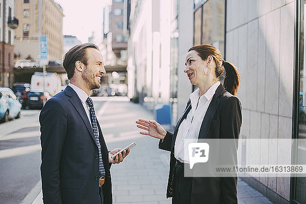 Smiling businesswoman talking to coworker in city