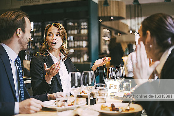 Businesswoman talking while gesturing by coworker in restaurant