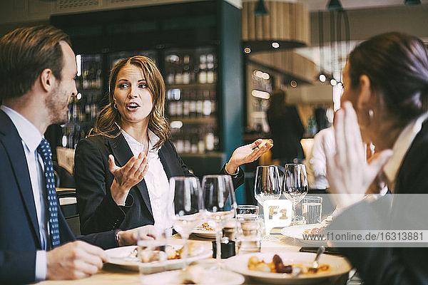 Geschäftsfrau spricht während einer Geste eines Mitarbeiters im Restaurant