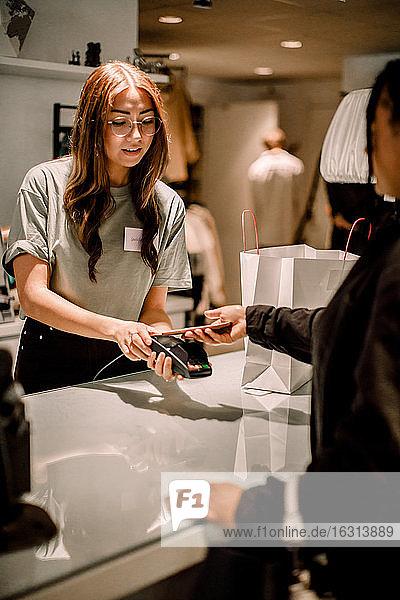 Weibliche Kundin bezahlt per Smartphone an Verkäuferin im Geschäft