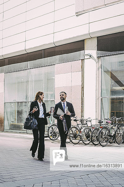 Businesswoman with coworker walking in city
