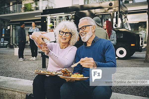 Lächelnde ältere Frau  die sich mit einem Mann beim Essen gegen einen Speisewagen in der Stadt vergnügt