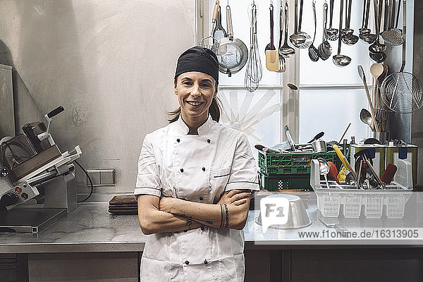 Portrait of smiling female chef with arms crossed in commercial kitchen