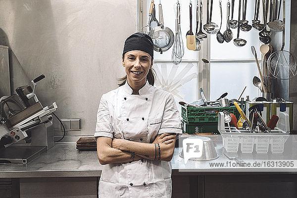 Porträt einer lächelnden Köchin mit verschränkten Armen in einer Großküche