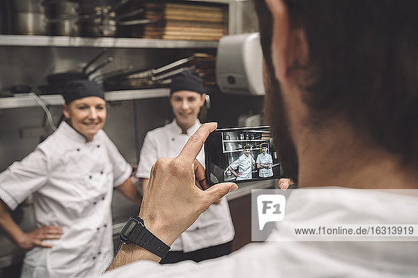 Male chef taking photograph of female coworkers in commercial kitchen