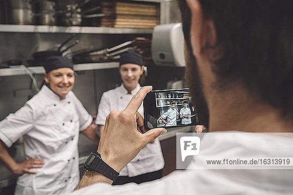 Männlicher Koch fotografiert weibliche Mitarbeiter in Großküche