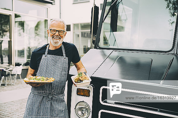 Smiling senior owner with food plate standing against commercial land vehicle