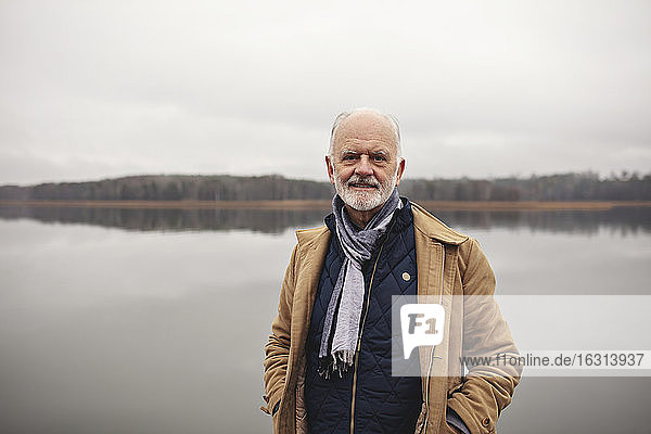 Portrait of smiling senior man with hands in pockets standing against lake
