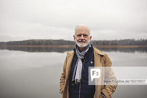 Porträt eines lächelnden älteren Mannes mit Händen in Taschen  der am See steht