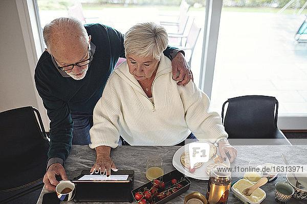 Hochwinkelansicht eines älteren Paares  das auf ein digitales Tablet schaut  während es am Esstisch im Wohnzimmer sitzt