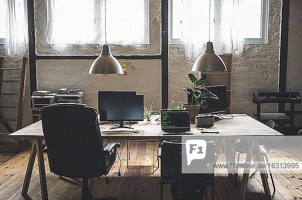 Laptop und Computer am Arbeitsplatz auf einem Tisch angeordnet nach Stühlen