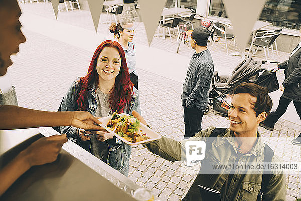 Female assistant giving food plate to smiling customer in city