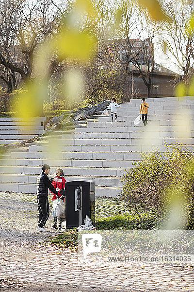 Männliche und weibliche Freiwillige werfen Plastikabfälle in den Mülleimer