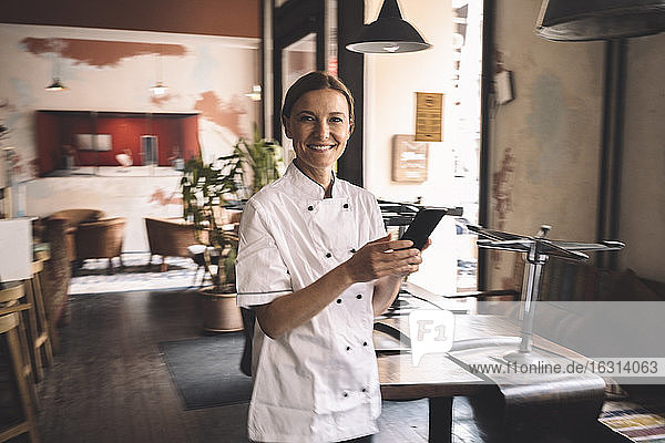 Portrait of smiling chef with smart phone in restaurant