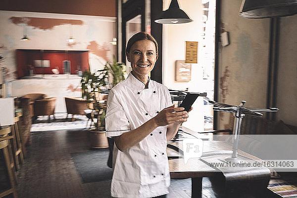 Porträt eines lächelnden Küchenchefs mit Smartphone im Restaurant