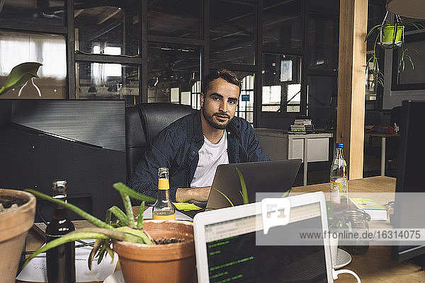 Portrait of businessman sitting at new workplace