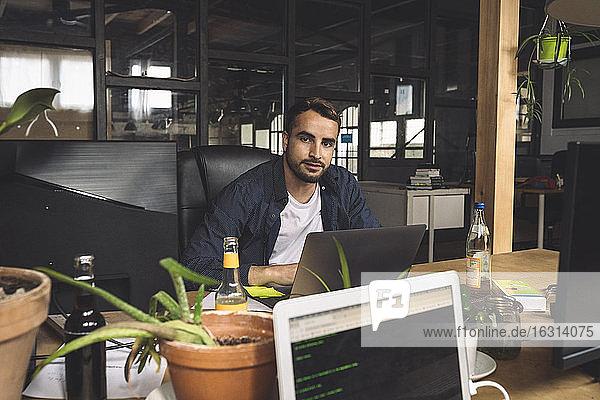 Porträt eines Geschäftsmannes  der an einem neuen Arbeitsplatz sitzt