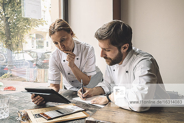 Chef looking at digital tablet while coworker writing at table in restaurant