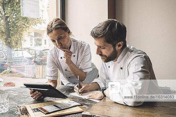 Chefkoch schaut auf digitales Tablett  während ein Kollege am Tisch im Restaurant schreibt