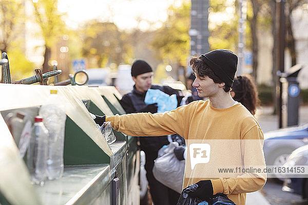 Lächelnder männlicher Umweltschützer wirft Plastikmüll in den Mülleimer