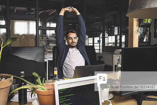 Freiberufler streckt sich  während er am Schreibtisch auf den Laptop schaut