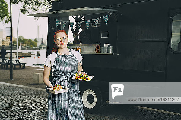 Portrait of smiling female owner holding indian food plate against commercial land vehicle