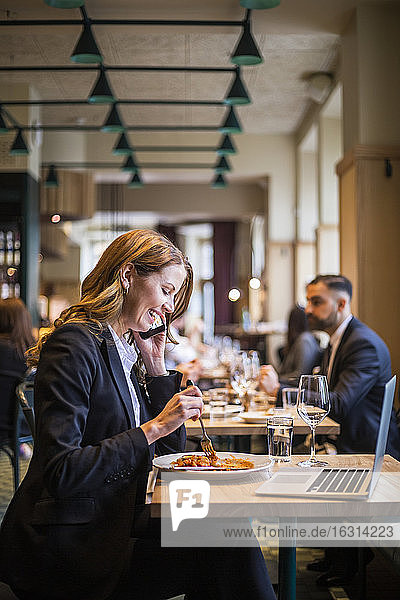 Smiling businesswoman talking on phone while eating in restaurant