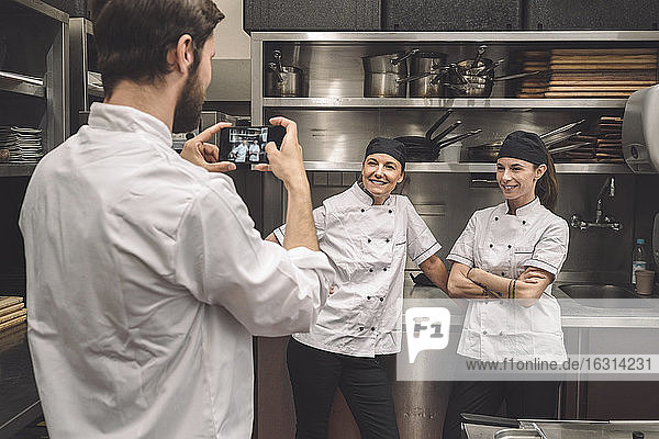 Male chef taking photograph of smiling female coworkers in commercial kitchen