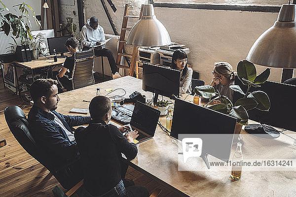 Männliche und weibliche Computerprogrammierer  die am Arbeitsplatz über dem Schreibtisch arbeiten