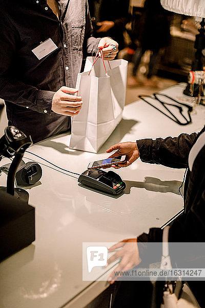 Schrägaufnahme einer Kundin  die im Geschäft über ein Smartphone bezahlt