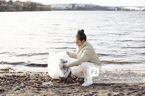 Junge Umweltschützerin sammelt Abfall  während sie am See kauert