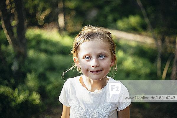 Porträt eines lächelnden Mädchens im Wald stehend