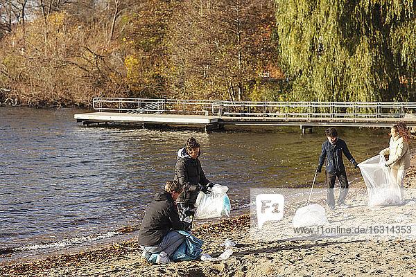 Männliche und weibliche Freunde sammeln Plastikmüll am See