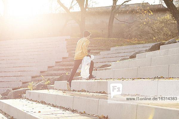 Männlicher Freiwilliger mit Plastikmüll beim Treppensteigen