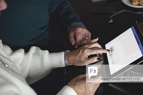 Älteres Ehepaar kauft zu Hause online über ein digitales Tablet ein