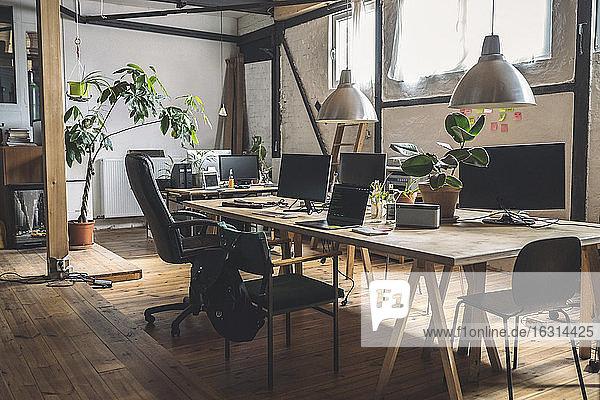 Leerer Laptop und Computer auf einem Tisch angeordnet nach Stühlen am Arbeitsplatz