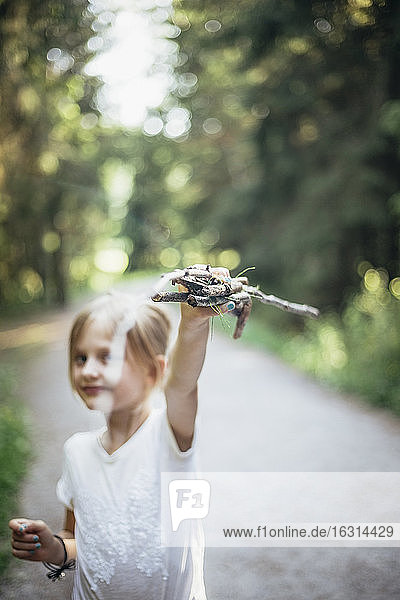 Portrait of girl showing sticks in forest