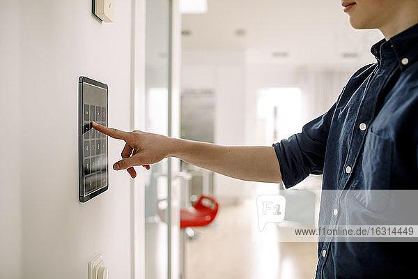 Mittendrin ein Teenager  der den Autorisierungscode über drahtlose Technologie an der Wand zu Hause eingibt