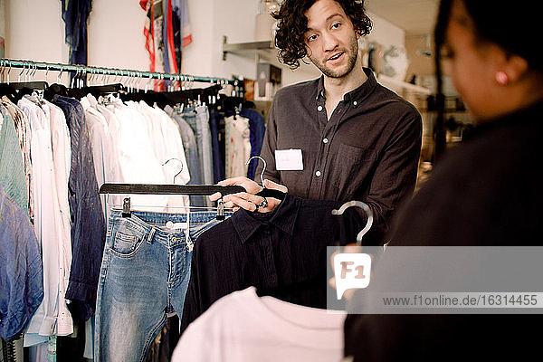 Verkäufer zeigt dem Kunden modische Kleidung im Geschäft