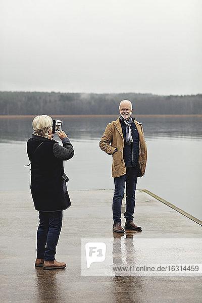 Ältere Frau in voller Länge fotografiert männlichen Partner am Seeufer bei klarem Himmel