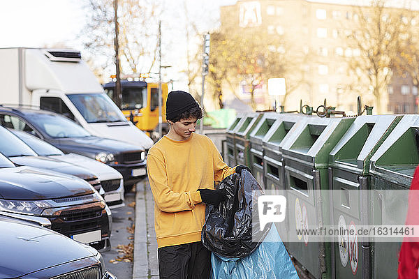 Young male volunteer holding waste in plastic bag by garbage can