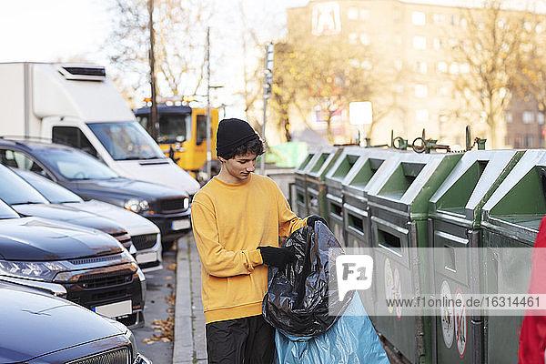Junger männlicher Freiwilliger hält Abfall in Plastiktüte an der Mülltonne