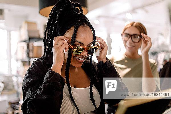 Lächelnde Freundinnen probieren Brillen aus  während sie sich im Modegeschäft unterhalten