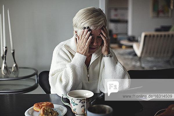 Besorgte ältere Frau mit dem Kopf in der Hand  die auf ein digitales Tablet schaut  während sie zu Hause am Esstisch sitzt